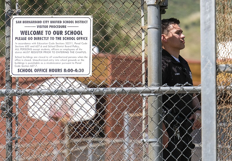 A police officer stands guard outside North Park School after a fatal shootin...