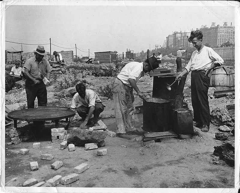 Residents of a Manhattan Hooverville preparing food in a mobile drum, in a ph...