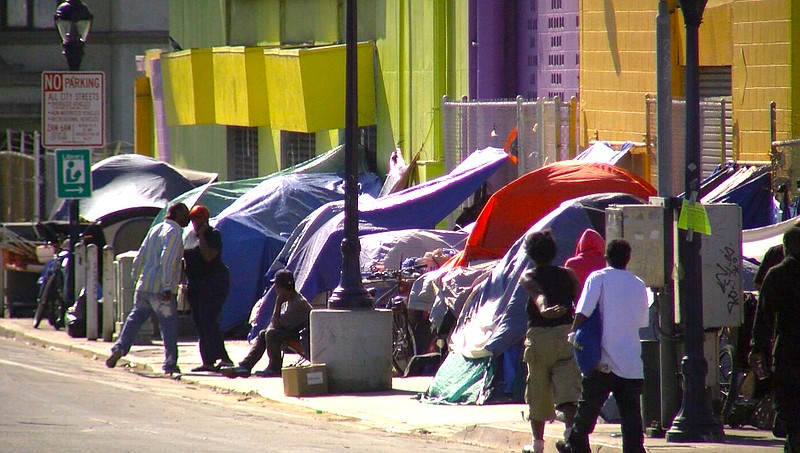 People stand outside of tents on 17th Street in San Diego's East Village, Nov...