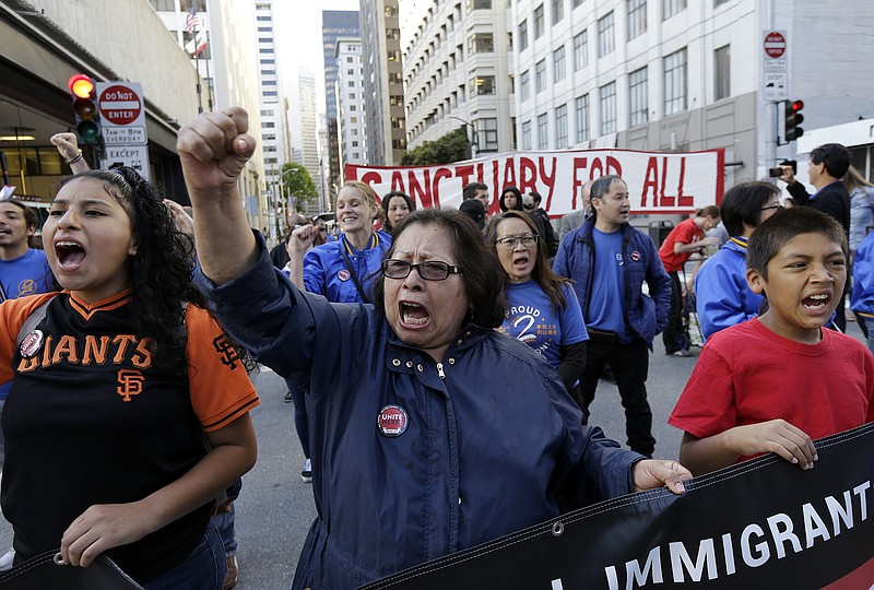 Guadalupe Chavez, center, and others yell during a protest outside of the U.S...