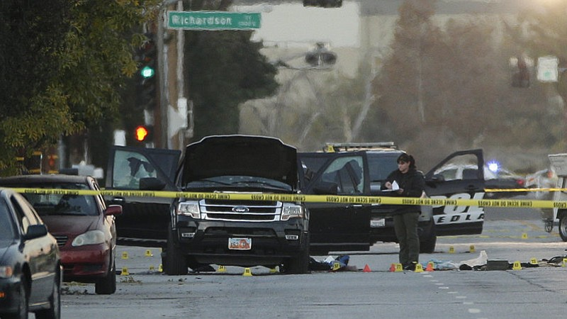 An investigator looks at a Black SUV that was involved in a police shootout w...