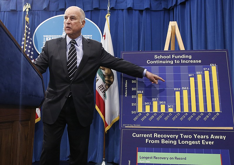 California Gov. Jerry Brown gestures to a chart showing the increase spending...
