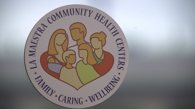 The logo for La Maestra Community Health Centers is seen on the front door of...
