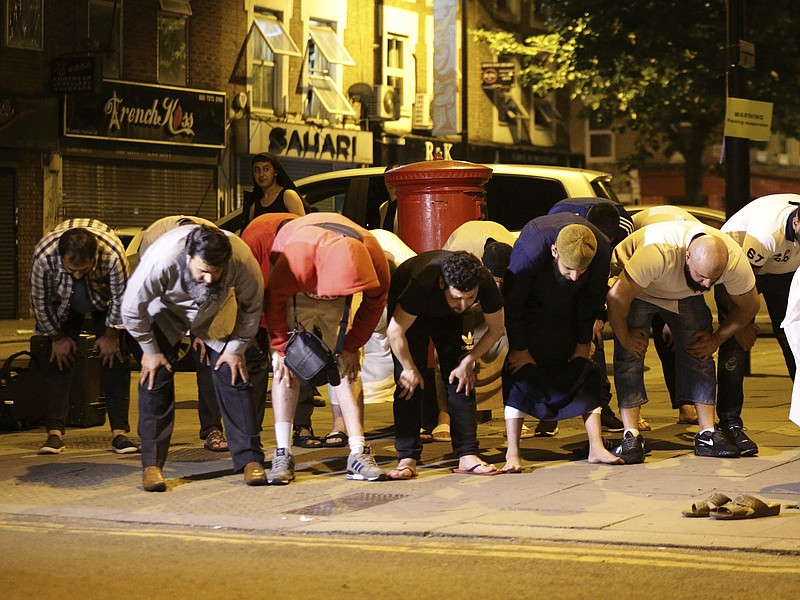 Local people observe prayers at Finsbury Park where a vehicle struck pedestri...