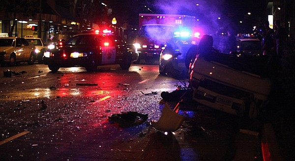 Police cars and an ambulance are seen at the site of a car crash in downtown ...