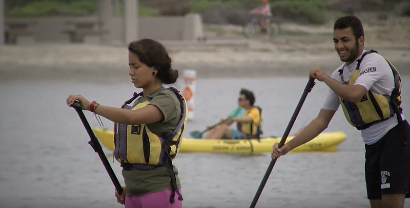 San Diego refugee high school students learn to paddle board on the San Diego...