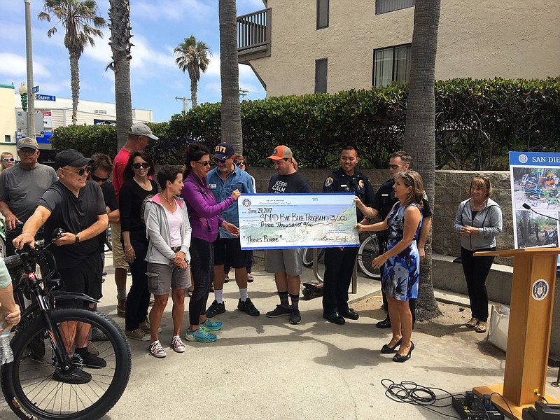 San Diego Councilwoman Lorie Zapf hands SDPD Bait Bike program operators a $3...