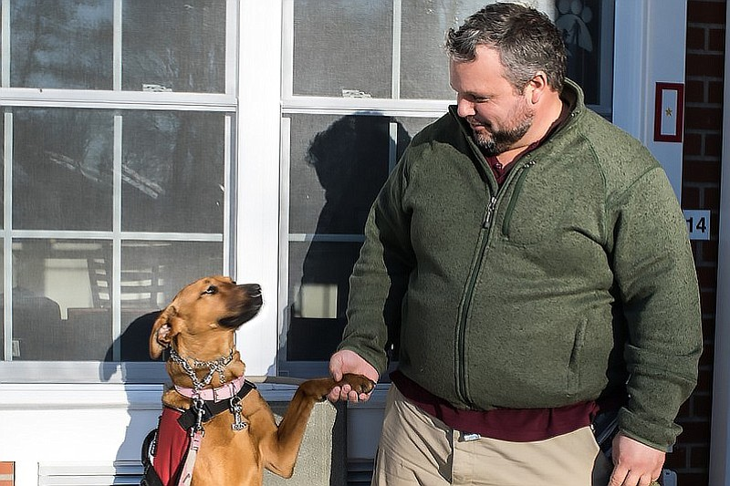 Army veteran Russel Keyser shakes hands with his dog, Artemis, outside of his...
