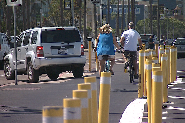 Two bicyclists ride along the Bayshore Bikeway at the intersection of West Gr...