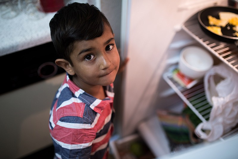 Daliya Ali's oldest son looks up from peeking into the refrigerator in his fa...