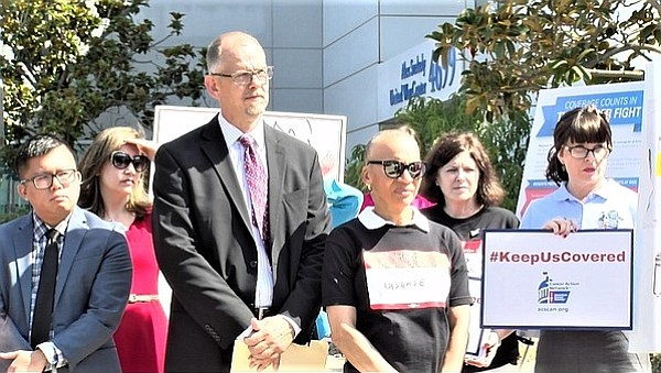 Members of the coalition San Diegans for Healthcare Coverage listen to a spea...