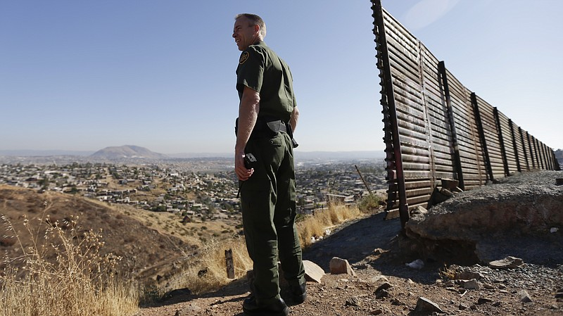 A U.S. Border Patrol agent looks out over Tijuana, Mexico, next to a portion ...