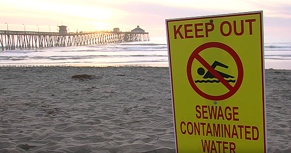 A beach closure sign is posted at Imperial Beach due to water pollution, Feb....