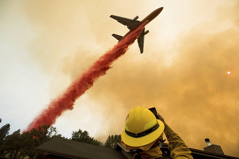 An air tanker drops retardant while battling a wildfire near Mariposa, Calif....