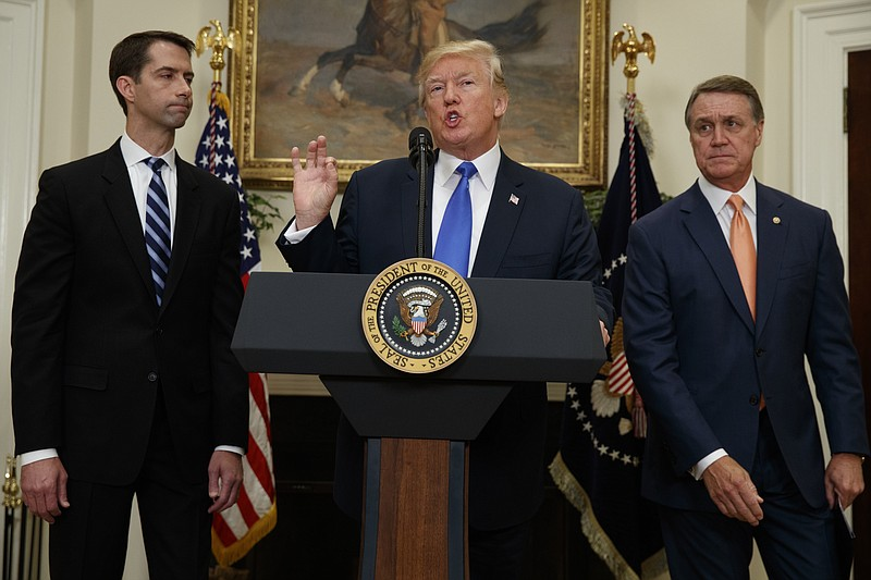 President Donald Trump, flanked by Sen. Tom Cotton, R- Ark., left, and Sen. D...