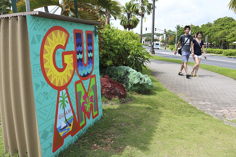 Tourists walk through a shopping district in Tamuning, Guam, May 15, 2017.