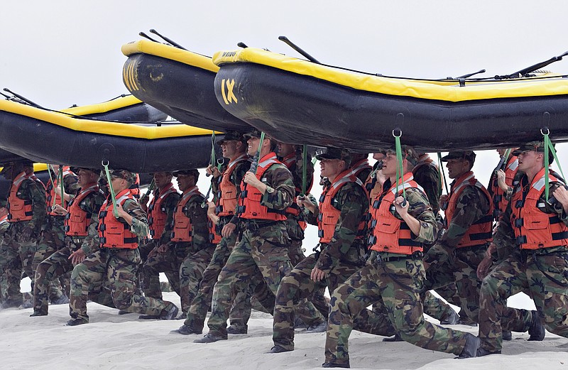 Navy SEAL trainees carry inflatable boats at the Naval Amphibious Base Corona...