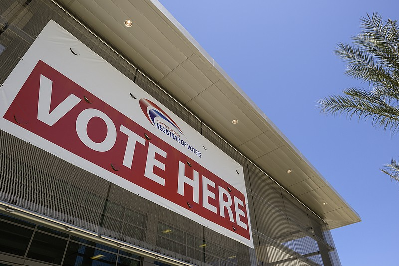 A 'vote here' sign hangs above the door at the San Diego County Registrar of ...