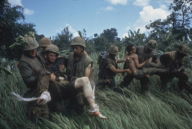 Marines carrying their wounded during firefight near the DMZ. 1966.
