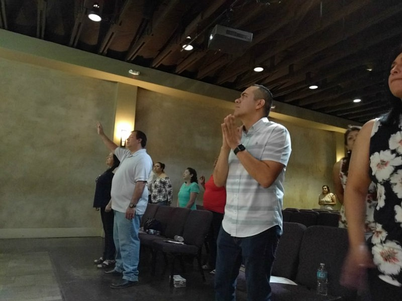 Alex Vaiz, senior pastor of Vida Church holds his hands in prayer, during a S...