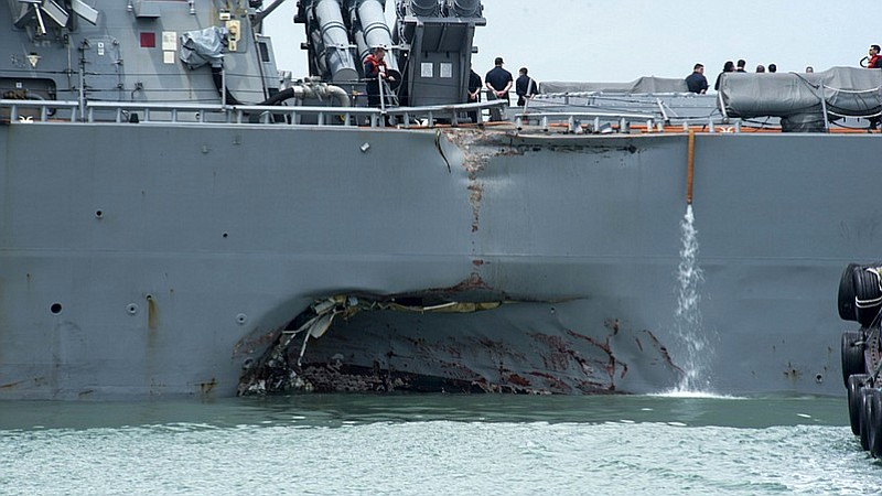 Damage to the port side is visible as the guided-missile destroyer USS John S...