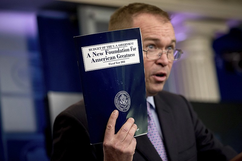Budget Director Mick Mulvaney holds up a copy of President Donald Trump's pro...