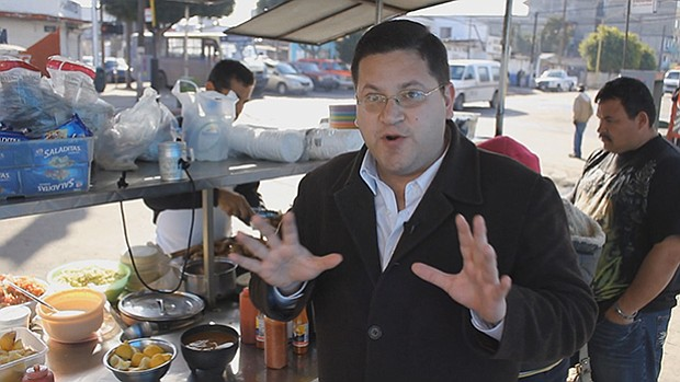 Host Jorge Meraz eating tacos from a street vendor, Tijuana, Mexico.