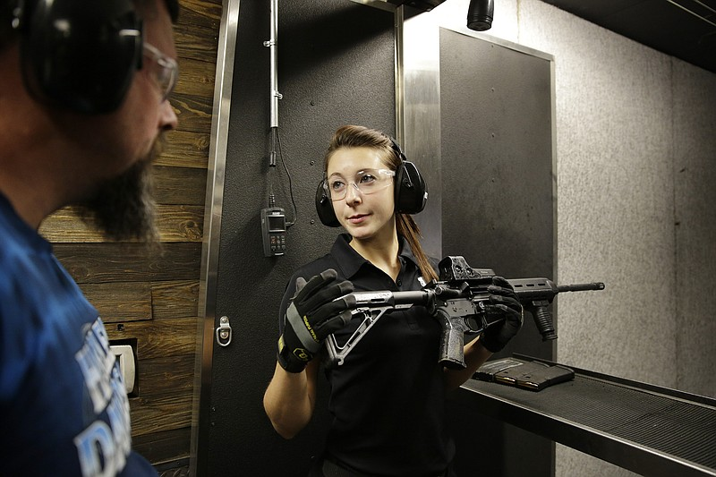 Shayna Zerbe, right, instructs Garret Sloan on how to fire a fully automatic ...