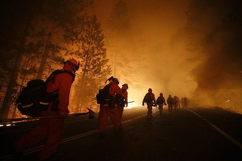 Inmate firefighters walk along Highway 120 after a burnout operation as firef...