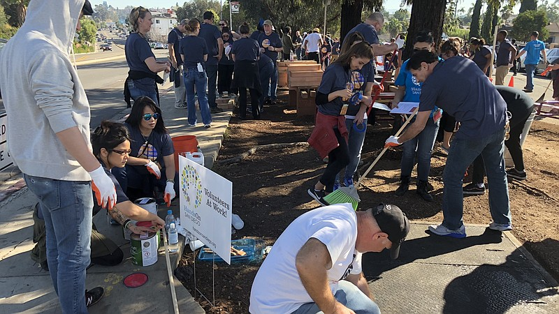 Volunteers work to pick up trash, build benches and paint near 50th Street an...