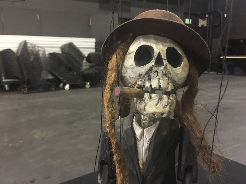 A hand carved marionette with dreadlocks and a cigar hanging from its mouth h...