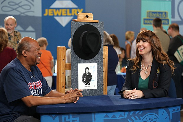 Laura Woolley (right) appraises a Michael Jackson-signed fedora and photo, ca...