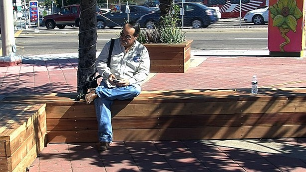 A resident sits on a bench at the corner of Euclid and Imperial avenues in Sa...