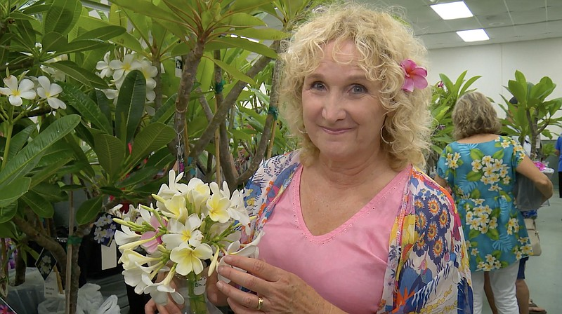Host Nan Sterman examines plumeria obtusa at Southern California Plumeria Soc...