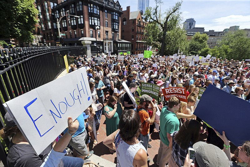 People rally outside the Statehouse, in Boston, Wednesday, June 20, 2018 to p...