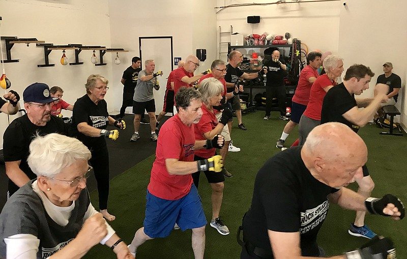 People with Parkinson's disease participate in a Rock Steady Boxing class, ta...