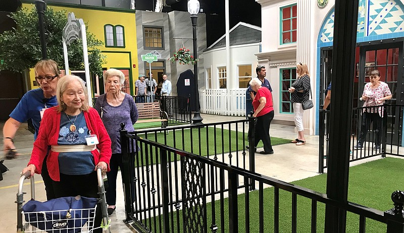 People walk around Glenner Town Square, a miniature village for Alzheimer's p...