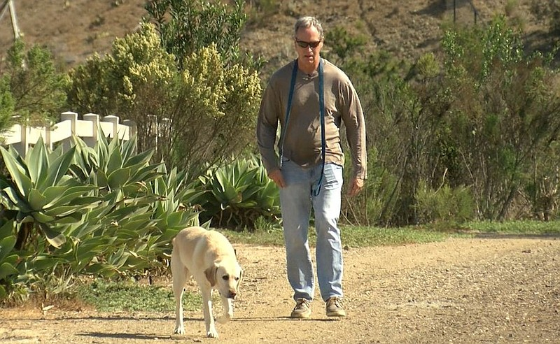Chris Whitmer, diagnosed with Parkinson's disease 12 years ago, walks along a...