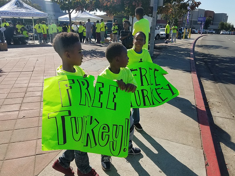 Kids hold signs for a turkey giveaway in the Lincoln Park neighborhood of San...