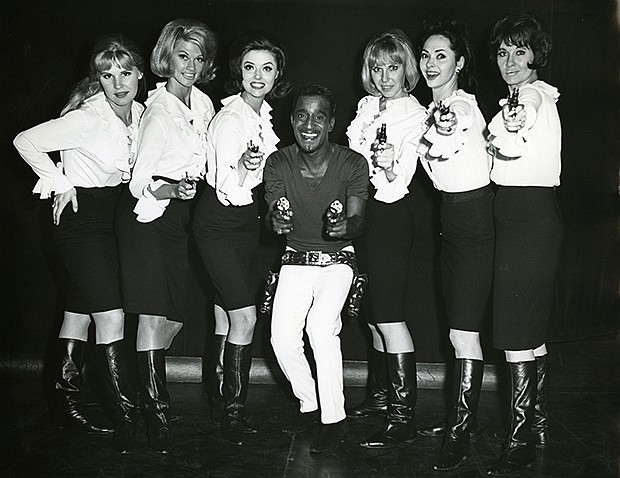 Sammy Davis, Jr. takes aim in a backstage photo with his dancers in a scene f...
