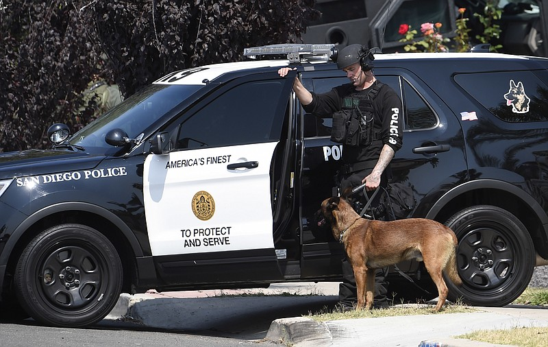 A San Diego police officer with a police dog waits outside a house with a pos...