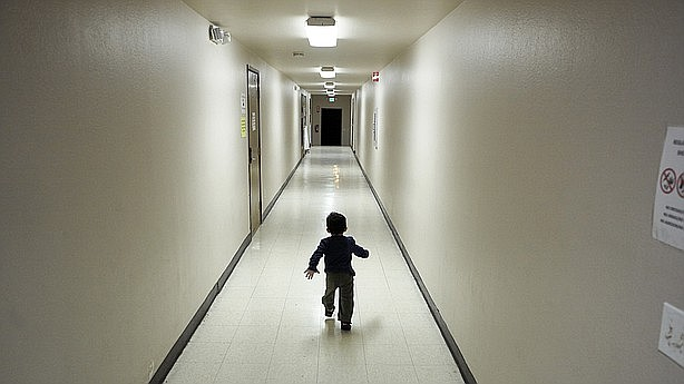 An asylum-seeking boy from Central America runs down a hallway after arriving...