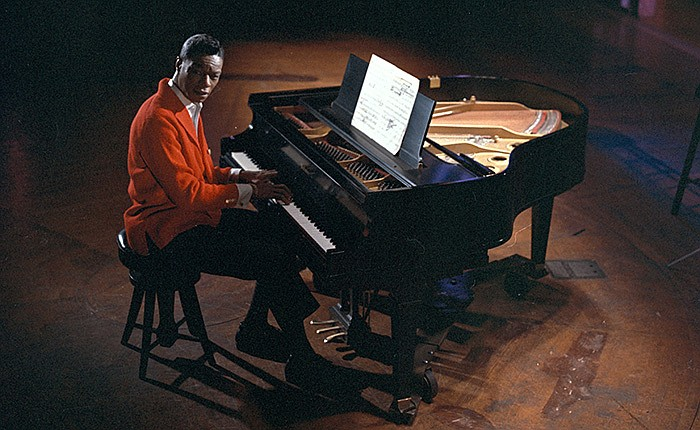 The legendary singer (seen sitting at a piano on stage) is celebrated on his ...