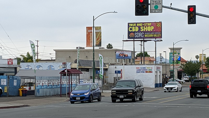 Cars in City Heights drive by a marijuana billboard advertisement on June 18,...