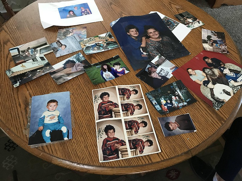 Photos spread out on the table at Colleen Khalifa's home show her son, Shawn,...