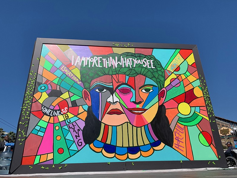 A colorful mural in downtown San Diego depicts a frowning face alongside a sm...