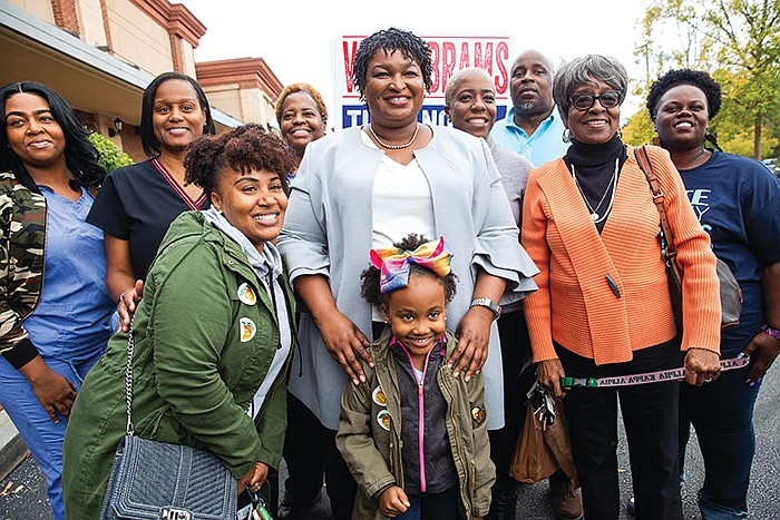 Georgia's Stacey Abrams (center) campaigns to become America's first black wo...