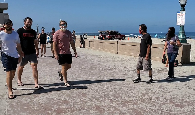 People walk on the Mission Beach boardwalk, July 11, 2020.