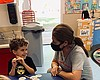 Holly Weber talks to a student at Magic Hours P...