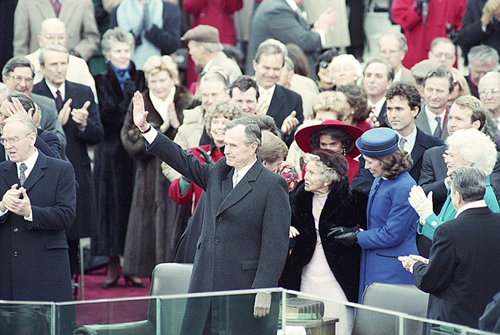 President George H. W. Bush waves after taking the oath of office, Jan. 20, 1...